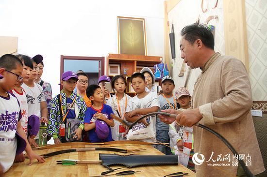 诺敏正在给从山东过来旅游的小朋友讲述弓箭的结构,他认为,弓箭的历史文化应该让更多宣传,这不光是蒙古族的文化,更是世界的文化。王慧 实习生 韩钰泽 摄