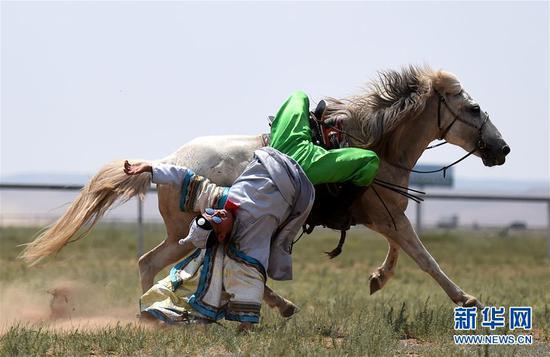 阿拉腾呼亚嘎在位于锡林浩特南部的凤凰马场为游客表演马术(7月2日摄)。38岁的阿拉腾呼亚嘎是锡林浩特市宝力根苏木的一名建档立卡贫困户。今年3月,他来到位于锡林浩特南部的凤凰马场上班,每月工资5000元。新华社记者 任军川 摄