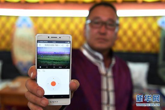 7月27日,内蒙古自治区鄂尔多斯市鄂托克前旗塔班陶勒盖查哈乃克布牧业合作社社员王楚格展示智慧放牧手机APP页面。