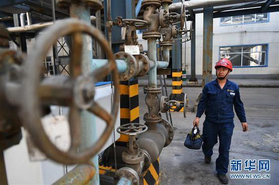 7月29日,一名工作人员从内蒙古鄂尔多斯市准格尔旗久泰能源内蒙古有限公司生产设备旁走过。