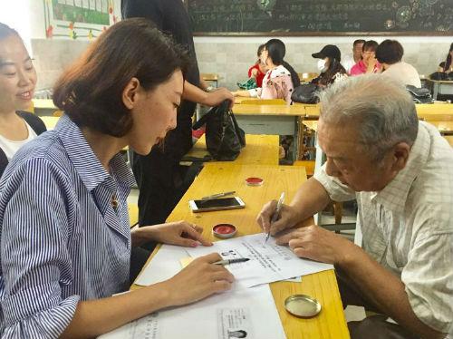 发放现场工作人员和陈志宏老人确认信息,并签字