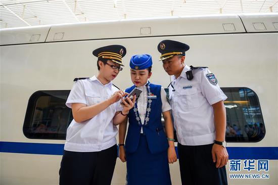 在呼和浩特东站,乘务组人员查看列车运行时间。