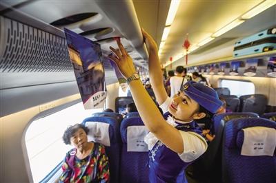 在乌兰察布开往呼和浩特东站的列车上,乘务员在整理行李架。