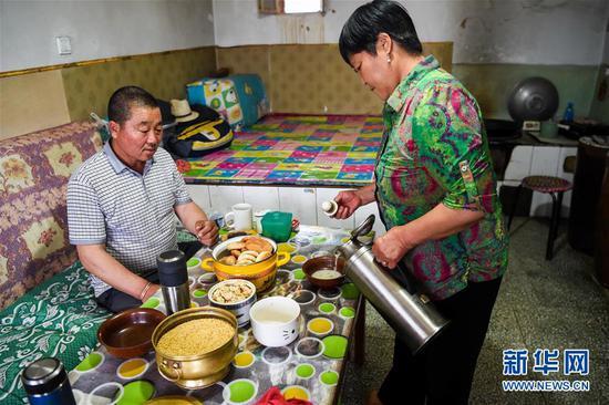 阿迪亚(左)和妻子娜仁其其格在家中喝奶茶(6月21日摄)。