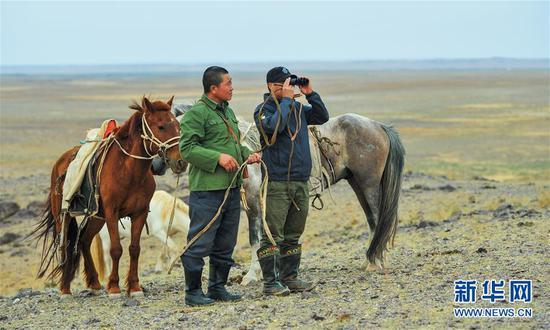 阿迪亚(左)和他的大儿子宾巴在边境线附近巡边(6月21日摄)。