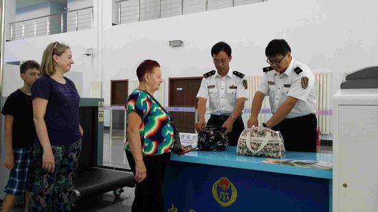 图为额尔古纳出入境检验检疫局工作人员在对黑山头口岸入境旅客所携包裹进行检疫查验