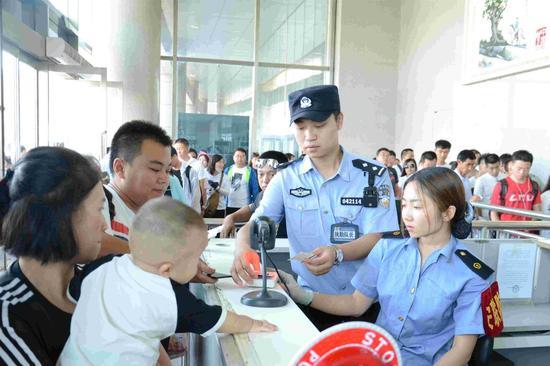 包头铁路公安处民警在包头站候车室检票口核对票证,确保票证人一致,全面加强车站管控力度