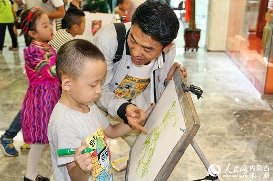 内蒙古晨旭艺校超级创意阁校长臧金龙出席活动现场并给孩子们指点绘画技巧