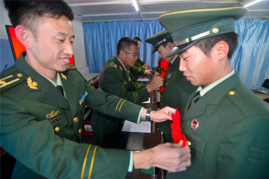 图为该站领导为退役士兵佩戴大红花