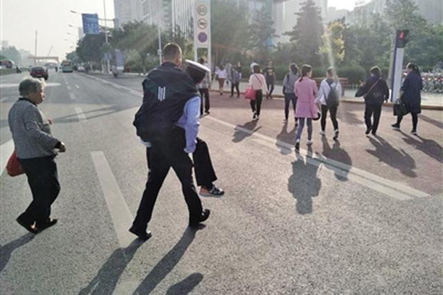 交警背半身不遂男子过马路 暖心场景微信朋友圈热传