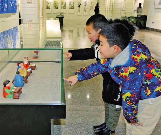 小朋友观看工艺品展览。