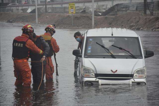 内蒙古自治区乌海市城区7人被困车内 消防人员蹚水探路救人