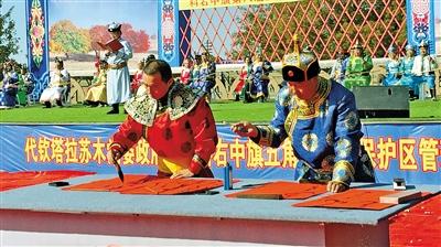 65岁的赵金海老人(右)在五角枫艺术节上用蒙古语挥毫泼墨