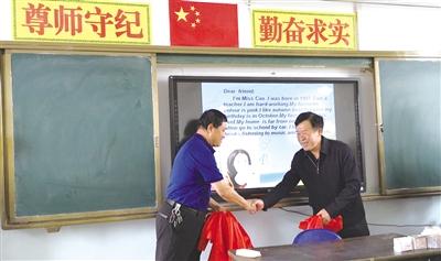 爱心人士(右)为智能教学设备揭牌   摄影/本报记者 郝儒冰