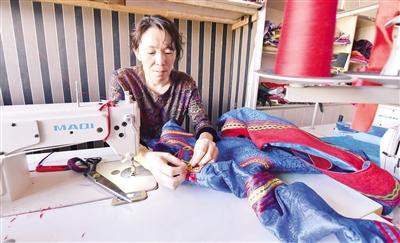 5月24日,呼和浩特市一家民族服饰店的服装设计师正在制作蒙古族服饰。