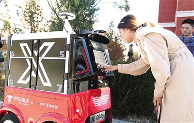 客户从机器人中取包裹。 本报记者 梁亮 摄