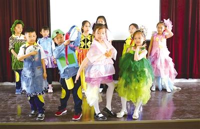 4月23日,孩子们展示用废旧物品制成的时装。