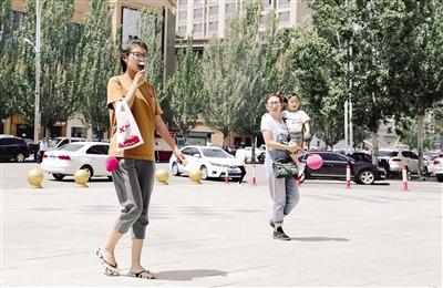5月14日,首府街头一位姑娘吃冰激凌消暑。摄影/本报记者 牛天甲
