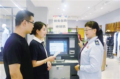 近日,涉税辅导员正在辅导回民区民族商场商户操作代开发票自助终端机。