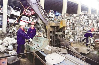 广州市金属回收有限公司购销部工人使用机械压缩拆解下来的汽车零部件,回收金属。