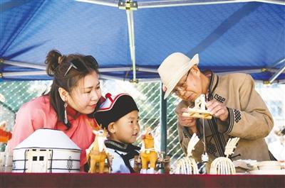 5月29日,在呼和浩特市蒙古族幼儿园北校区,非遗传承人正在介绍非遗作品。