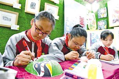 呼和浩特市玉泉区石头巷小学的同学绘制京剧脸谱。