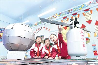 """4月24日,内蒙古航天小学的学生在""""红领巾航天梦想园""""参观航天模型。"""