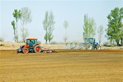 呼和浩特市和林格尔县,大型机械正在翻地和播种。
