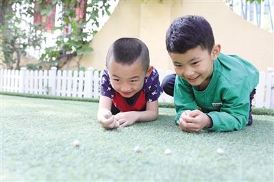5月9日,两个孩子在打弹珠。