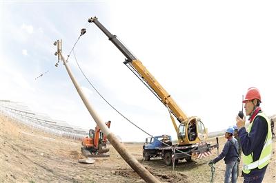 5月21日,锡林郭勒盟太仆寺旗青岛昌盛太仆寺旗24万千瓦光伏扶贫项目现场,施工人员与太仆寺旗供电分局的工作人员正在进行线路改造。