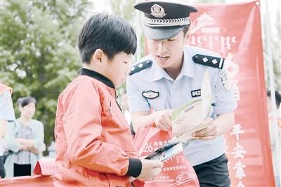 5月26日,铁路公安民警向小朋友普及安全常识。摄影/本报记者 刘晓君