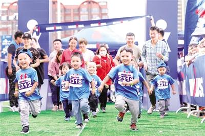 5月27日,小朋友在世界小铁人中国赛·呼和浩特站比赛中快乐奔跑。 于涛 摄