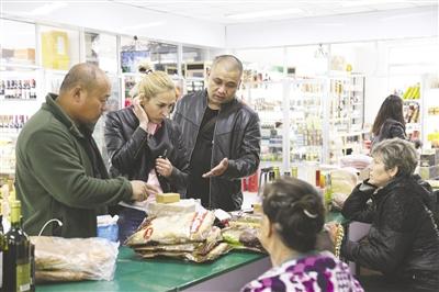 5月29日,俄罗斯游客正在满洲里市中俄互市贸易区选购商品。