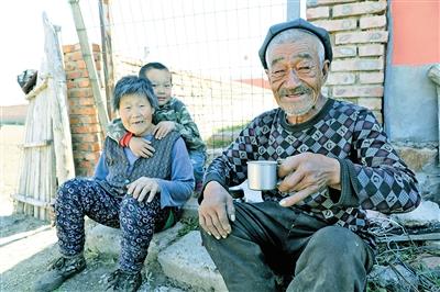 程少华(右一)和老伴及孙子程凯在自家菜园旁边休息。
