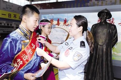"""禁毒民警为""""义务禁毒宣传员""""佩戴绶带。摄影/本报记者 刘晓君"""