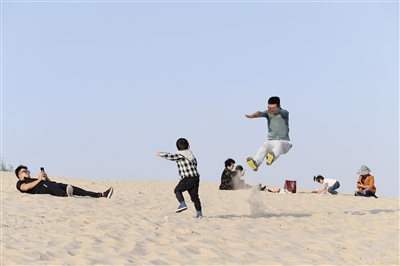 10月6日,通辽市库伦旗银沙湾景区,游客在体验沙漠冲浪。本报记者 金泉 摄
