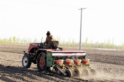 农民正在忙碌地机械播种。