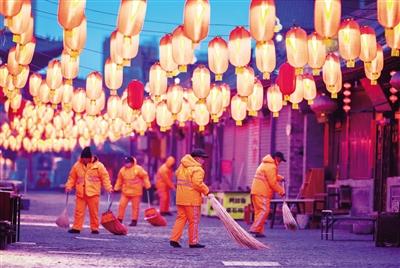 2月4日,环卫工人在呼和浩特市玉泉区塞上老街清扫街道。 当日是农历大年三十,各行各业的很多工作人员仍坚守在岗位上。 ■新华社发(丁根厚 摄)