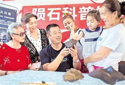 7月20日,内蒙古陨石学会会员在为居民讲解陨石知识。摄影/本报记者 牛天甲