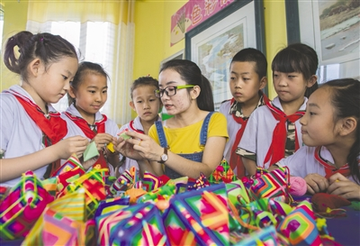 """6月12日,五塔寺东街小学学生在老师的指导下制作创意""""龙舟""""。王磊 摄"""
