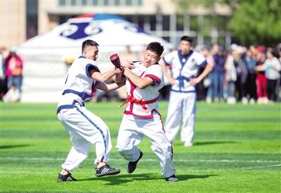 """5月23日,学生正在进行传统项目""""抢枢""""运动表演。王磊 摄"""