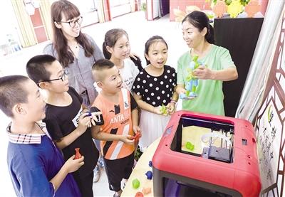 8月9日,小朋友们正在学习和体验3D打印技术。摄影/本报记者 牛天甲