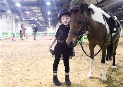 5月22日,一位小朋友与她骑的小马培养感情。摄影/本报记者 牛天甲