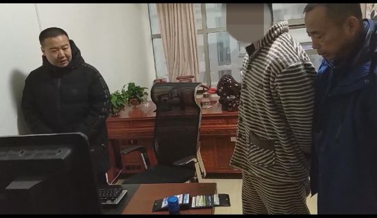 图为民警对嫌疑人涉案电脑进行检查。