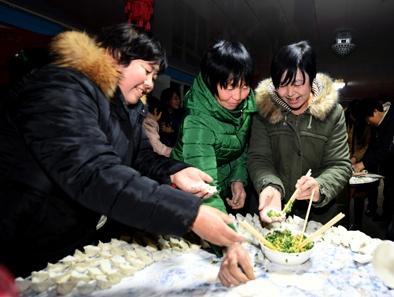 1月16日,几名妇女在上黄花塔拉嘎查集体过大年活动中包饺子。本报记者任军川摄