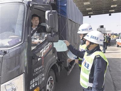 路政执法人员向货车司机发放宣传单 摄影/本报记者 张学博