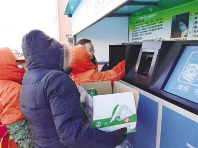 村民争相将分好类的垃圾投放进智能垃圾回收箱