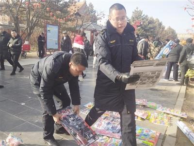 城管队员帮助占道摊贩收起经营物品