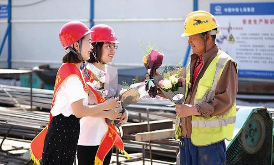 在呼和浩特地铁工地,志愿者们将鲜花送给建设工人。