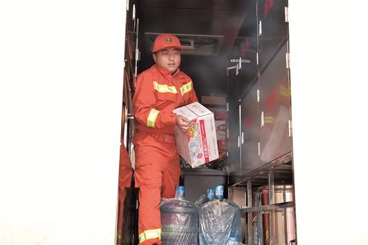 消防战士搬运运抵的救援物资。(本版照片均由记者安吉斯摄)